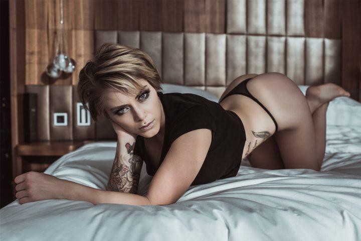 Красивая девушка в черной маечке и в трусиках стрингах выгнулась как кошка на кровати.