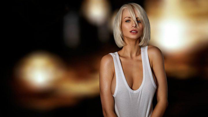 Стройная блондинка в белой маечке на голые сиськи.