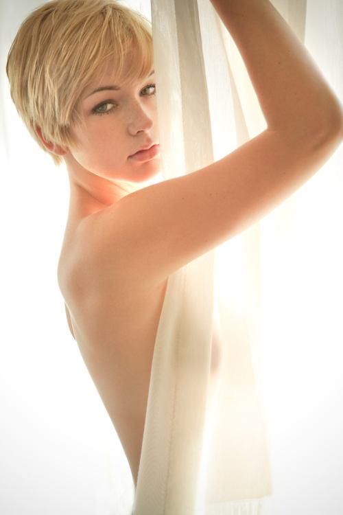 Обнаженная девушка с короткими белыми волосами закрылась прозрачной тканью.