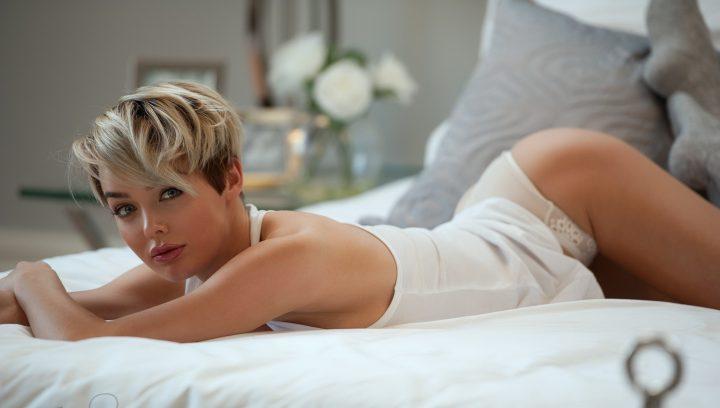Красотка блондинка с пухлыми губами и красивой попой лежит на белой простыне.