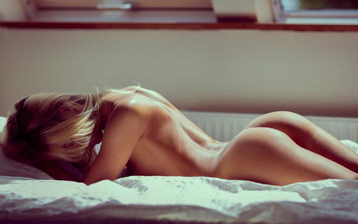 Таинственная девушка с голой круглой попой нежится в кровати.