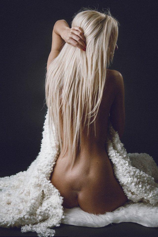 Длинноволосая блондинка обнаженная укрывается мягким пледом.