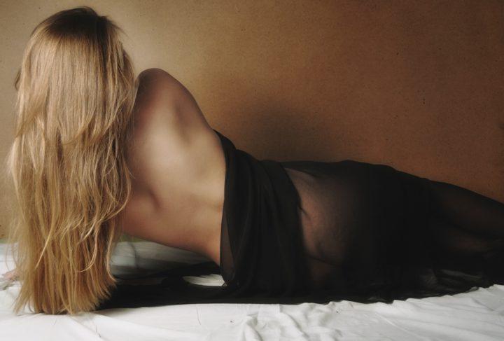 Девушка с натуральными белыми волосами лежит на боку спиной в черной прозрачной ткани.