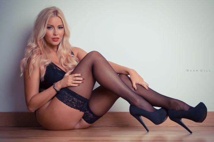 Прекрасная незнакомка с белыми волосами сидит голой попой на полу в чулках и туфлях на высоком каблуке.