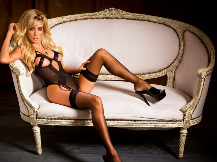 Красотка в шикарном белье сидит в будуарном кресле в очень сексуальной позе.