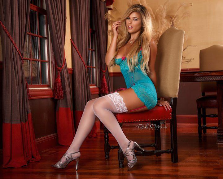 Сексуальная красотка сидит на стуле в соблазнительном бирюзовом белье и белых чулках.