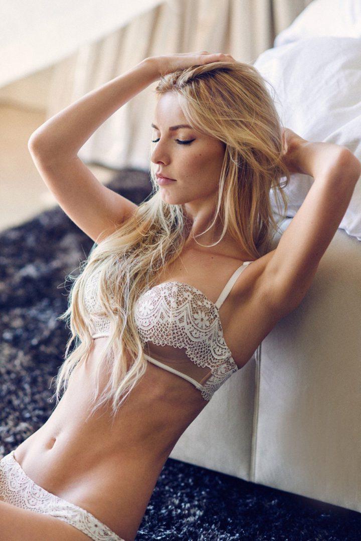 Красивая блондинка сидит на полу з закрытыми глазами.