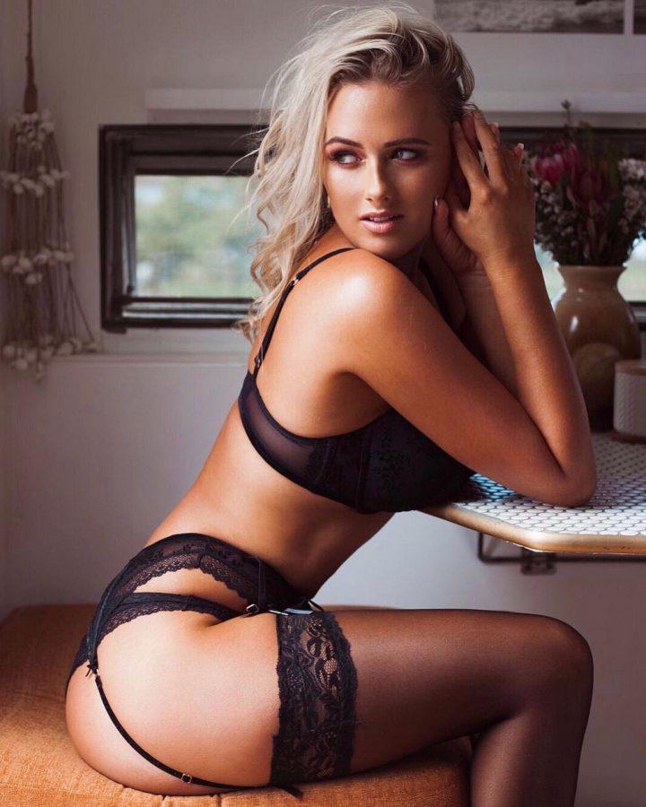 Красотка в одном нижнем кружевном белье сидит за столом и смотрит в сторону.