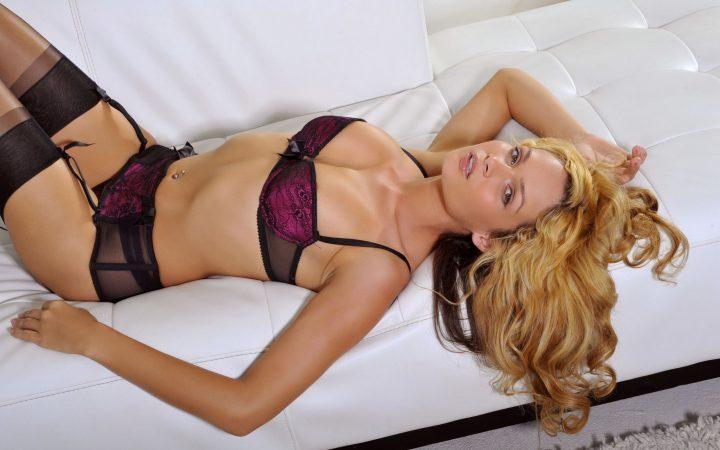 Красивая девушка с пшеничными волосами в сексуальной позе лежит на диване.