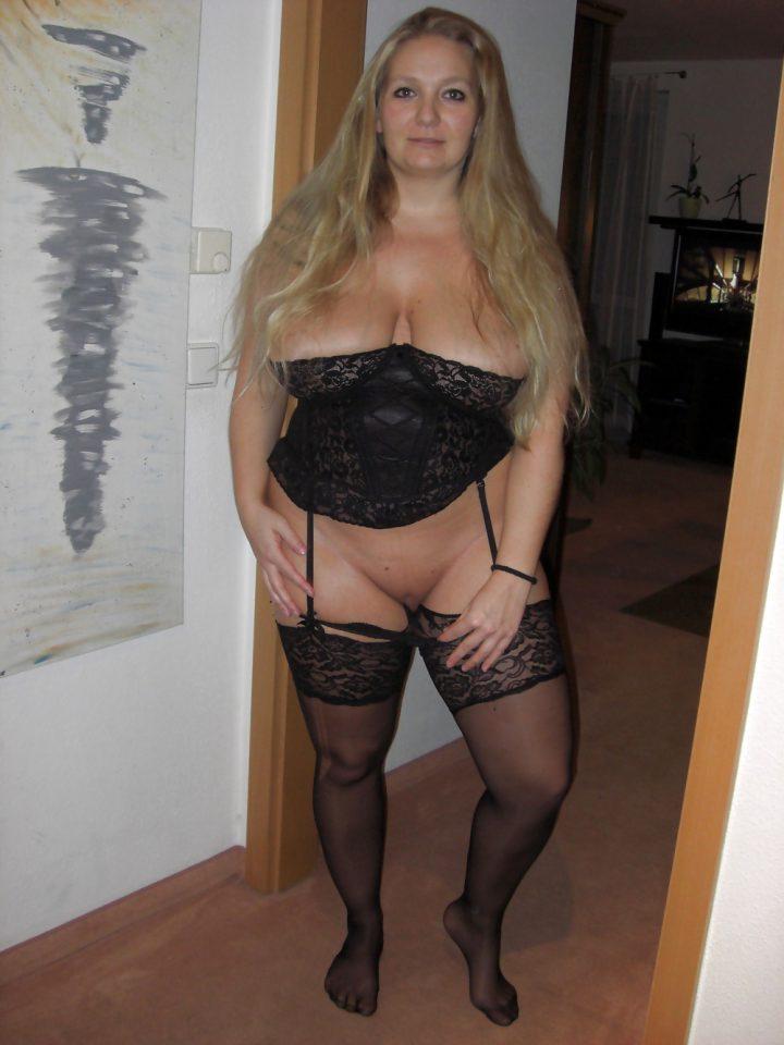 Сексуальная женщина с длинными белокурыми волосами в корсете и в чулках без трусов