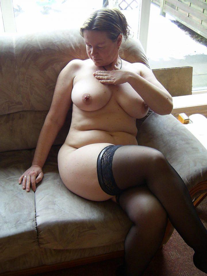 Милфа без комплексов сидит обнаженная на диване и любуется своими сиськами