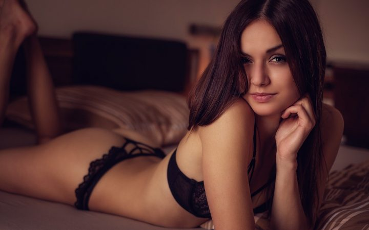 Молодая брюнетка в эротическом белье мило улыбается.