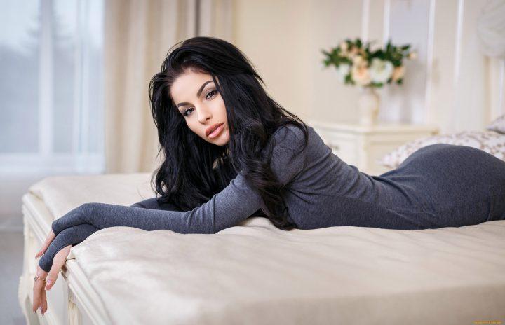 Жгучая брюнетка в облегающем платье лежит в постеле.