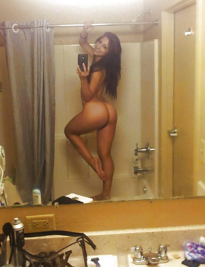Девушка стоит в ванной с голой попой делает селфи.