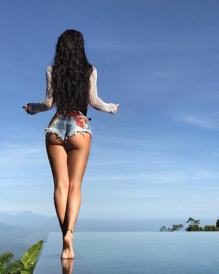 Девушка с красивыми волосами и аппетитной попкой в  мини шортиках стоит спиной.