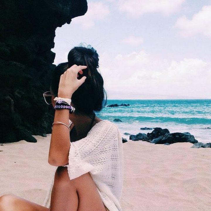 Молодая девушка с пучком на голове сидит на песке и любуется скалами.