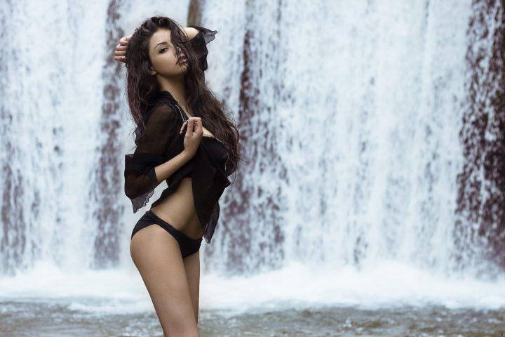 Красотка в прозрачной блузке гуляет у водопада.