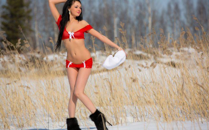 Красотка в красном белье без куртки гуляет по зимнему лесу.