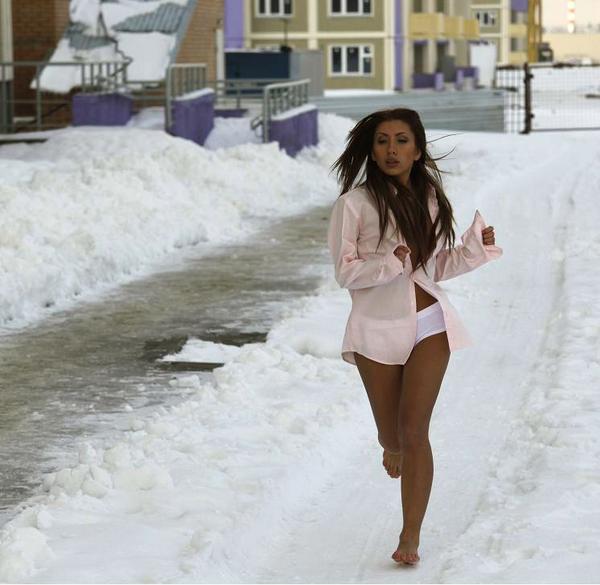 Соблазнительная брюнетка в белых трусиках и розовой рубашке бежит по снегу.