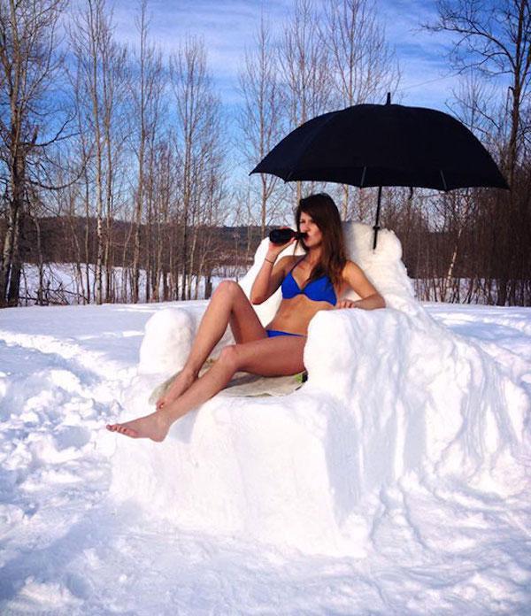 Девушка в купальнике сидит в кресле из снега и пьет пиво.