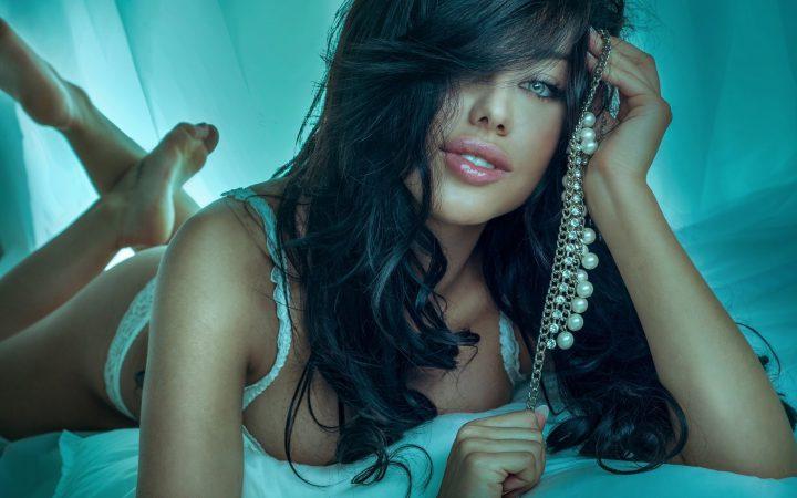 Кудрявая брюнетка с сексуальными губами лежит на кровати с украшением в руках.