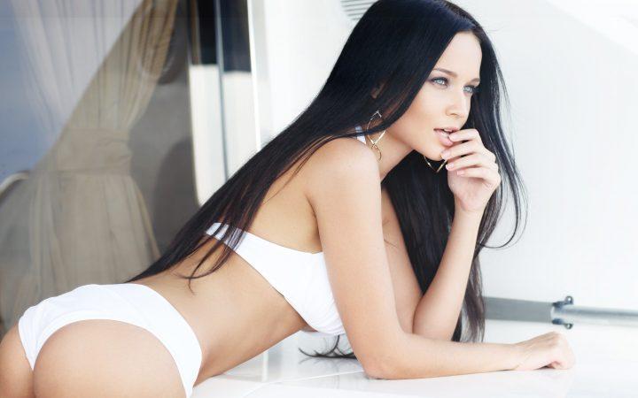 Красотка с длинными волосами и пухлыми губами нагнулась в белом купальнике.