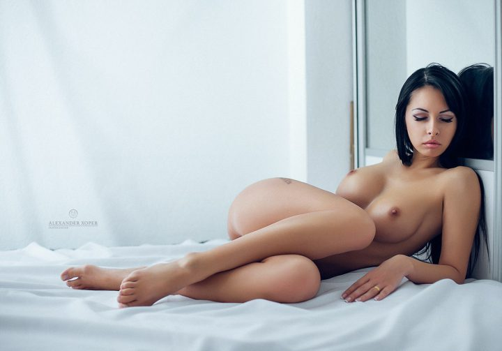 Брюнетка голая с закрытыми глазами лежит на кровати.