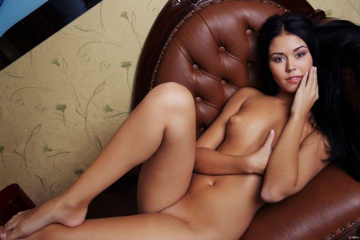 Брюнетка с хитрыми глазами голая лежит на диване и закрывает рукой маленькую грудь.
