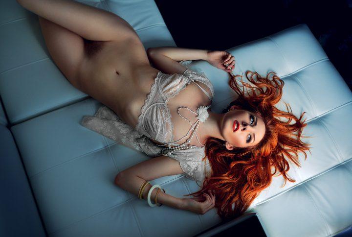 Рыженькая красотка лежит на белом диване с не бритым лобком без трусиков.