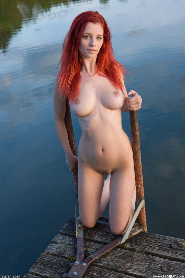 Рыжая русалка обнаженная хочет искупаться в водоеме.