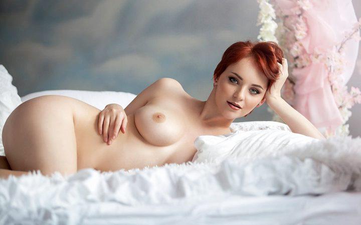 Рыжая чертовка с короткой стрижкой лежит на постели голая.