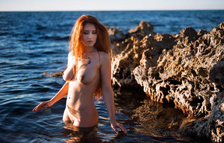 Рыжая девушка с длинными волосами ниже плеч купается в море без одежды.