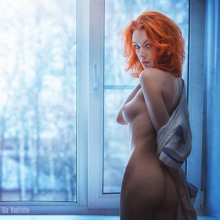 Худенькая девушка с маленькой грудью стоит у окошка.