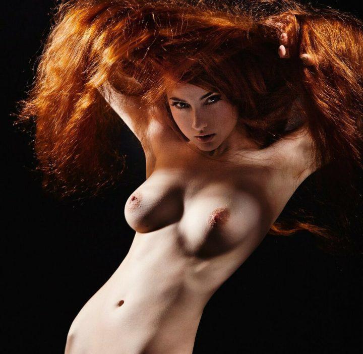 Стройная обнаженная красотка с длинными рыжими волосами.