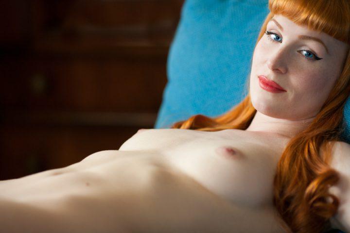 Женщина с идеальной прической лежит без одежды.