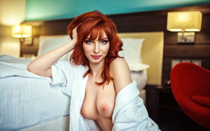 Яркая женщина красотка сидит на полу у кровати в рубашке на голое тело.