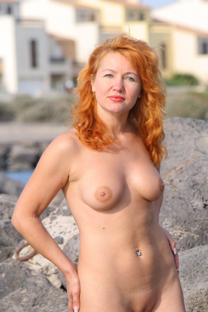 Смелая женщина с сережкой в пупке голая загорает.