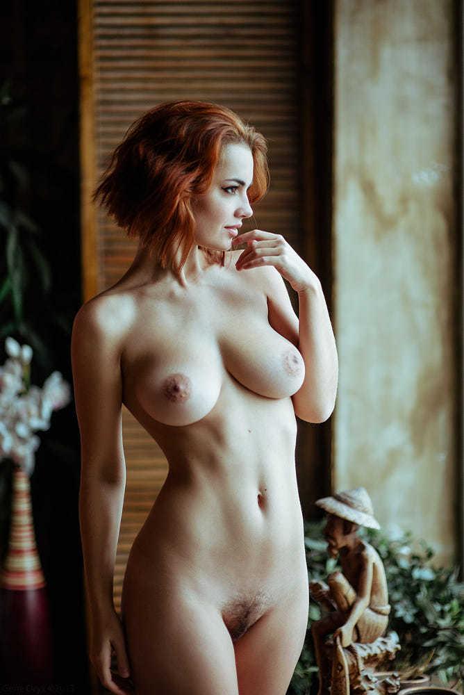 Загадочная женщина с короткими рыжими волосами голая смотрит куда то в даль.