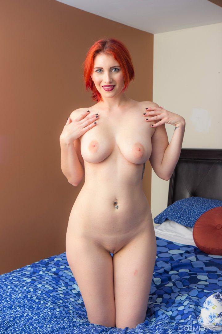 Женщина с яркими рыжими волосами положила руки себе на грудь и улыбается.