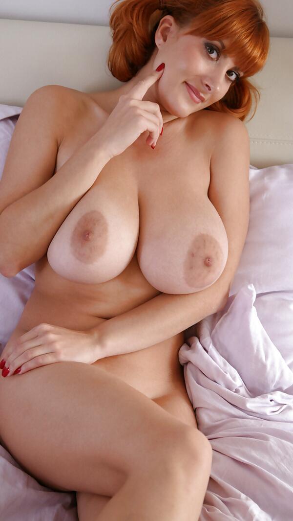 Женщина в игривом настроении с большими сиськами голая лежит в кроватке.