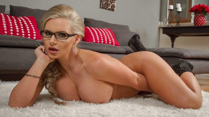 Сексуальная женщина в очках лежит на белом ковре