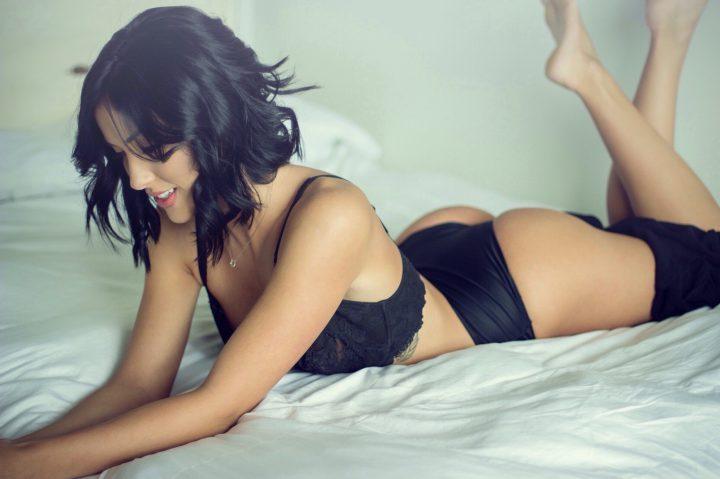 Стеснительная девушка с короткими волосами лежит на кровати.