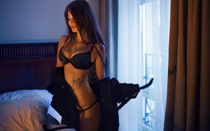 Сексуальная девушка с татуировкой на животе снимает халат.
