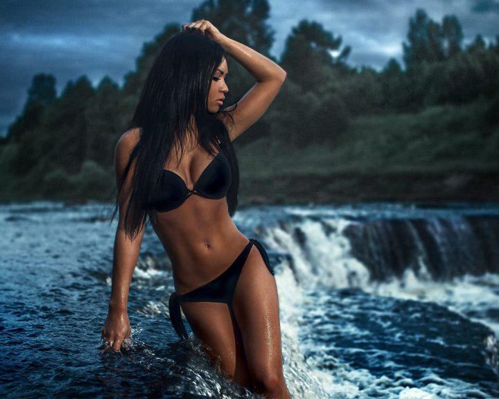 Красивая и мокрая стройная девушка стоит в водопаде.