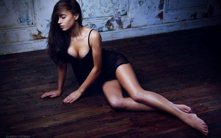 Прекрасная брюнетка в черной комбинации сидит на полу.