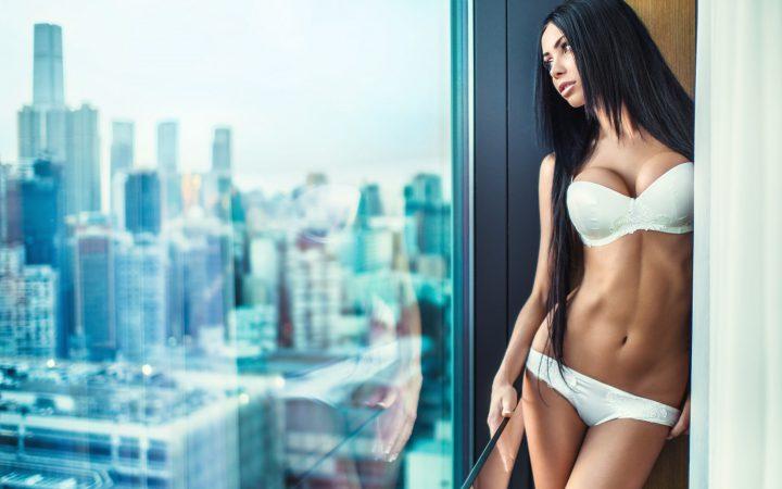 Задумчивая девушка в белом лифчике и трусиках смотрит в окно.