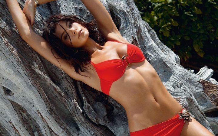 Брюнетка в красном купальнике лежит на коряге дерева.