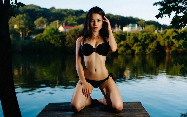 Стройная брюнетка азиаточка в черном купальнике сидит на мостике у воды.