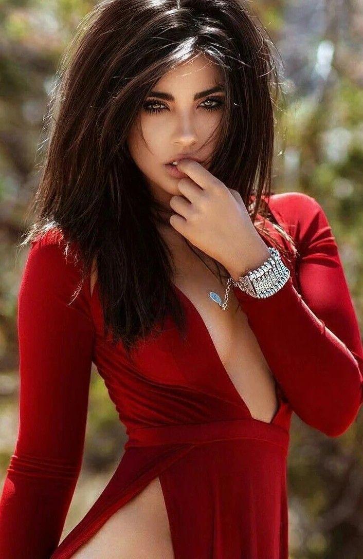 Сексуальная брюнетка в красном откровенном платье очень красива.