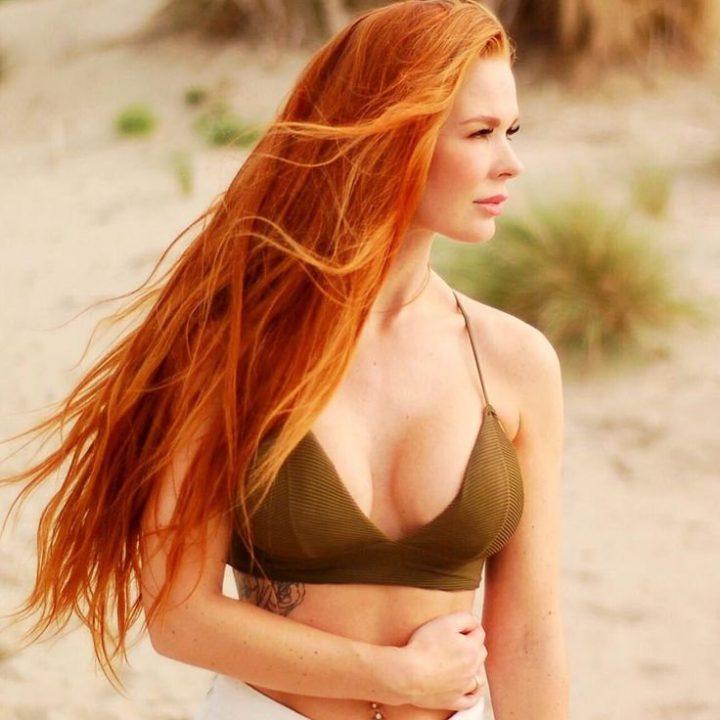 Красивая девушка с длинными рыжими волосами в оливковом бюстье.
